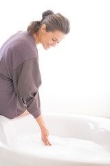 Happy young woman preparing bathtub