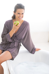 Happy young woman with apple sitting on bathtub