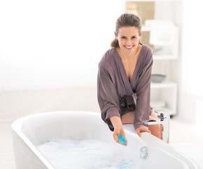 Happy young woman adding bath salt in bathtub