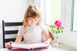 Interior portrait of a cute little girl reading a book
