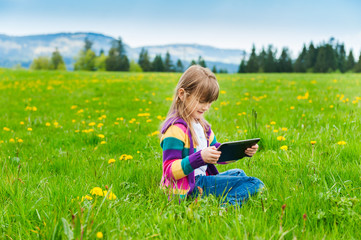 Outdoor portrait of a cute little girl playing with tablet pc