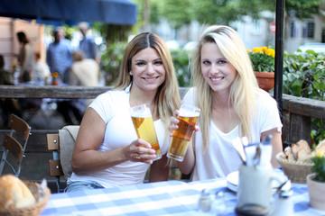 Zwei glückliche Mädchen sitzt im Biergarten