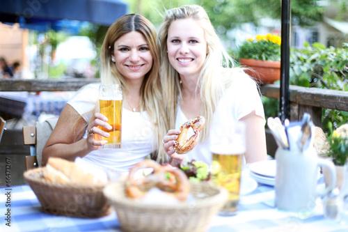 canvas print picture Zwei glückliche Mädchen sitzt im Biergarten