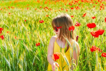 Portrait of a cute little girl playing in a poppy field