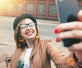 City lifestyle stylish hipster girl using a smartphone taking ph