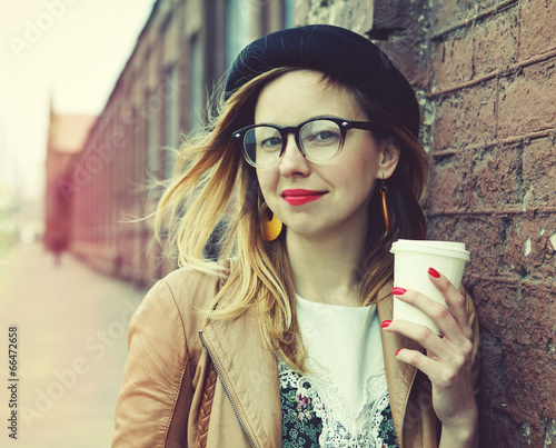 Stylish woman in the street drinking morning coffee - 66472658