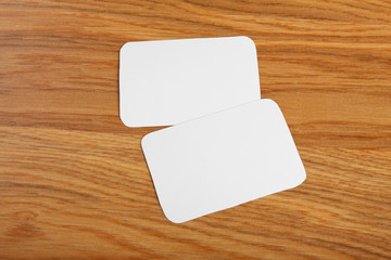 blank business cards with rounded corners on a wooden background