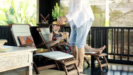Couple drinking juice, relaxing on terrace in tropical place