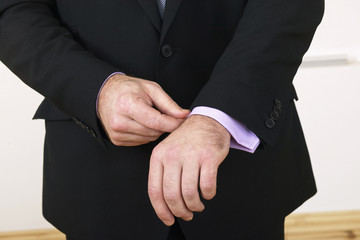 close up of businessman adjusting his cufflinks