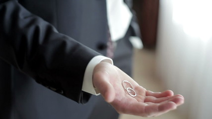 man in a suit holding a two wedding rings