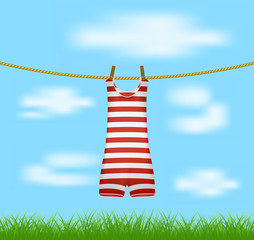Striped retro swimsuit hanging on rope