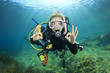 Leinwandbild Motiv Young woman scuba diving signals okay