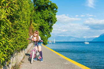 Outdoor portrait of a cute little girl on a bicycle