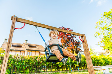 Cute toddler boy having fun on a swing