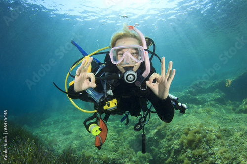 In de dag Duiken Young woman scuba diving signals okay