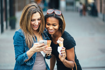 Multi ethnic Friends eating ice cream in city and texting