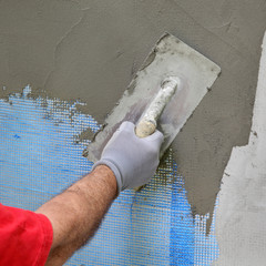 Wall insulation, mason worker spreading mortar over mesh