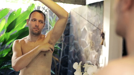 Man applying antiperspirant on his armpit in the bathroom