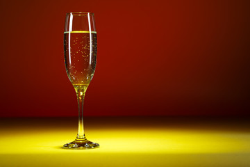 Glass of champagne on colorful background. Glass of bubbly.