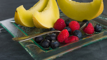 Fresh fruit on a glass dessert plate on black background.