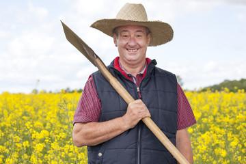 Man with straw hat in rape field