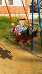 ребенок качается на качелях на детской площадке