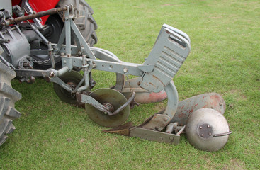 A Vintage Plough on the Back of a Farming Tractor.