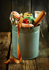 Bucket with tools for sewing.