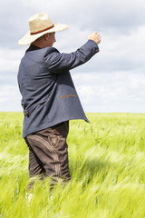 Man with hat pointing in the corn field