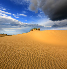 dunes in sandy desert under thunder sky