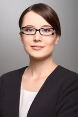 Attraktive stilvolle junge Geschäftsfrau mit einer Brille