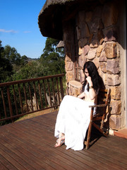 Thoughtful girl in white clothes sitting on the veranda