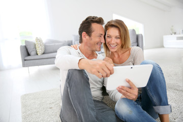 Middle-aged couple websurfing with tablet at home