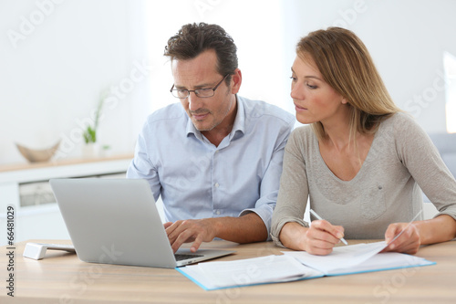 Couple at home working on laptop computer - 66481029