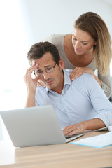 Woman trying to relax worried husband in front of laptop