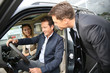 Car dealer showing vehicle binnacle to clients