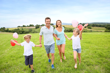 Family running in countryside, kids holding balloons