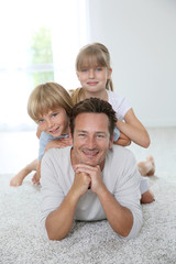 Daddy with kids laying on carpet