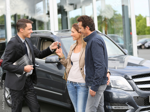 Salesman in car dealership giving keys to clients - 66481408