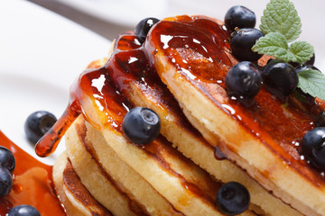 Pancake delicious with blueberries, mint and syrup macro