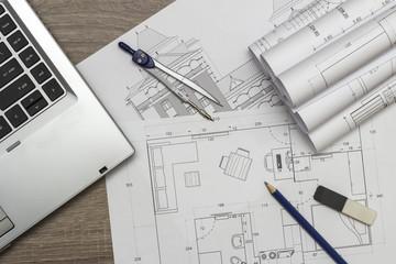 Architecture blueprints and laptop