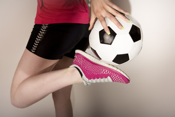 Sportliche junge attraktive Frau mit Fußball
