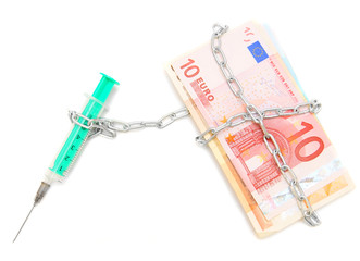 Syringe is chained by a chain to banknotes (euro).