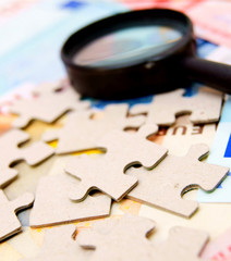 Puzzle and magnifier on documents.