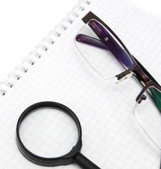 Magnifier and glasses on a notebook.