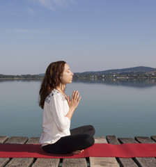 Young caucasian woman meditating on a summer day by a lake