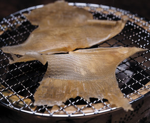 Slices of dried fish on grill, close up