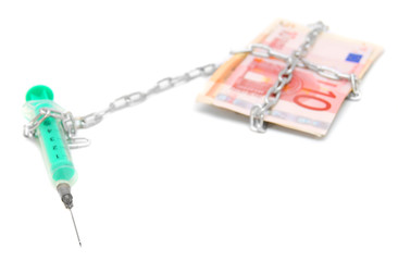 Syringe, chain and pack of euro of banknotes.