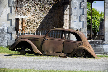 Side view of a rusty old car in Oradour sur Glane, France.