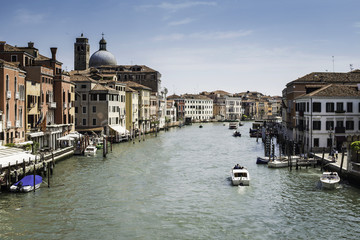 Ancient buildings and boats in the channel in Venice